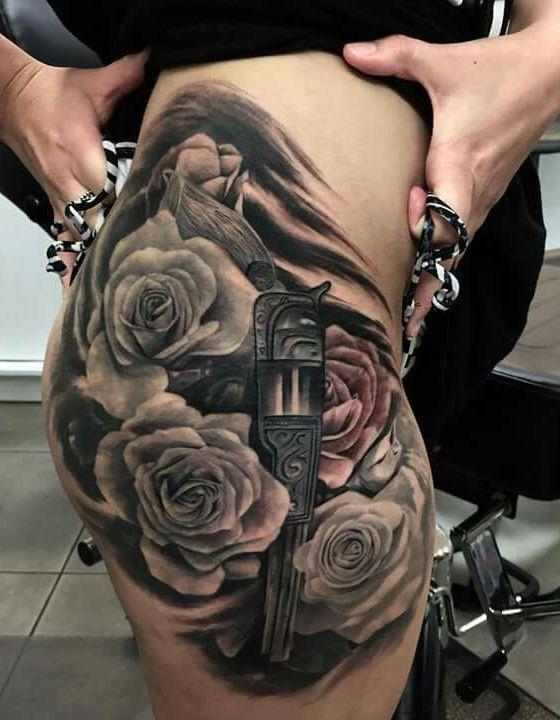 róże i rewolwer tatuaż na biodrze