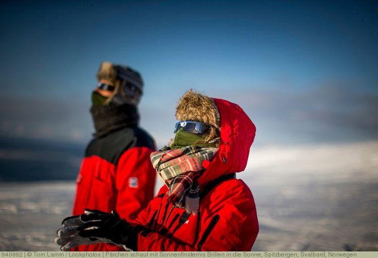 Pärchen schaut mit Sonnenfinsternis Brillen in die Sonne, Spitzbergen, Svalbard, Norwegen