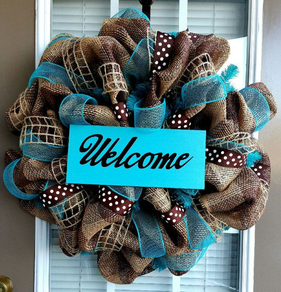 This wreath is made with a durable burlap deco mesh, coordinating ribbons, and a wooden hand painted vinyl sign. This is a large wreath which measures approximately 26x 26x 6. We would be happy to make the sign with a name or monogram instead of the welcome sign; include a note when checking out if youd prefer something different. Please note: Exact ribbons may not always be available and may be substituted for ribbons in similar patterns and colors.