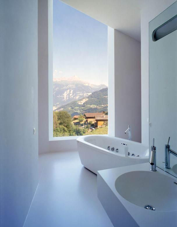 This minimalist white bathroom enjoys a view over the Swiss countryside -  Architecture by Bonnard Woeffray Architects