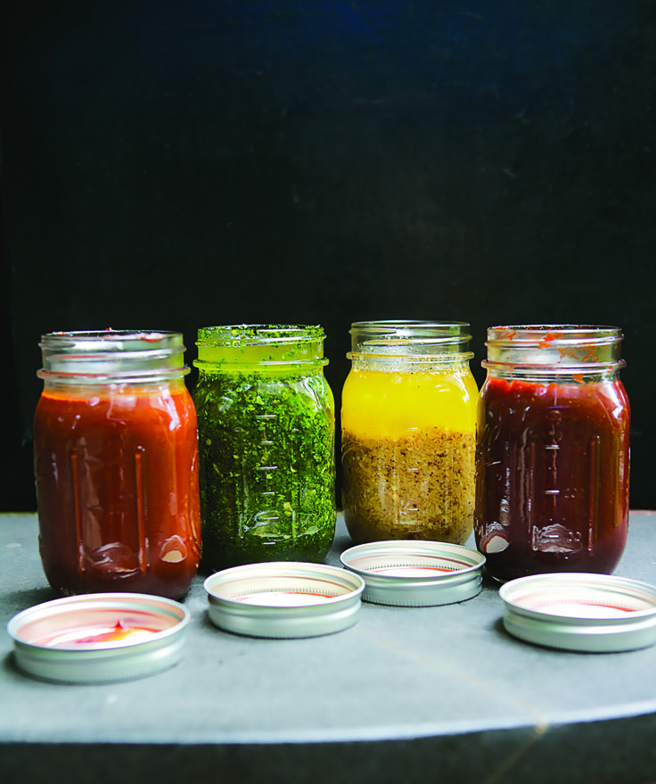 "Chef Rick Bayless' four secret weapons – (from left) red chile adobo, green chile adobo, roasted garlic mojo and dark chipotle – are featured in his new book, ""More Mexican Everyday."""
