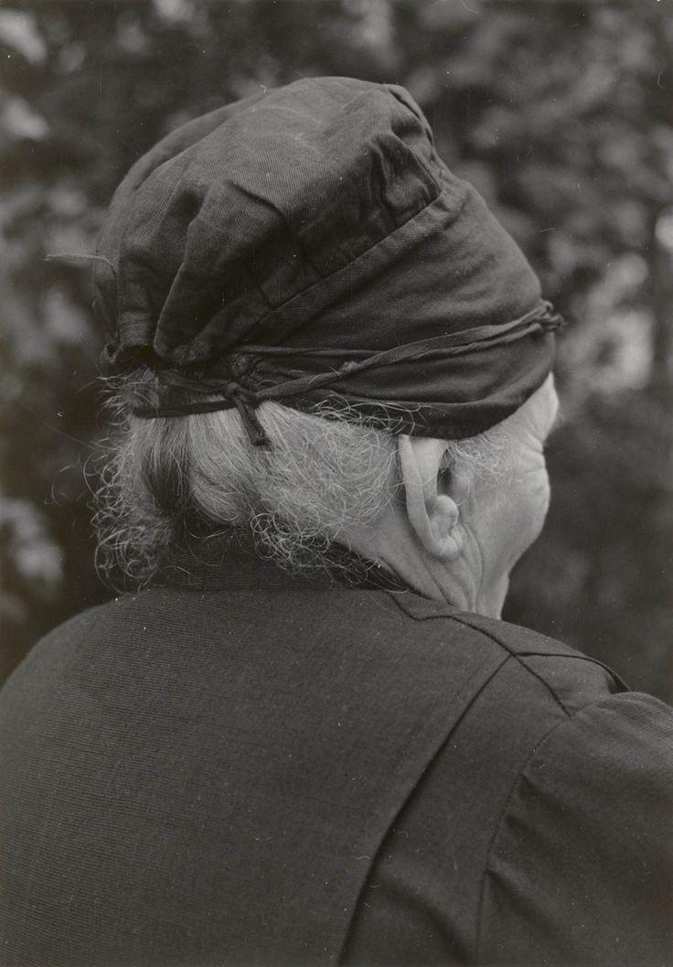 Mevrouw Kee van Eekelen-De Kok uit De Kladde (N-B) demonstreert opzetten van strakke muts en dubbele muts. Haar in knot vrij hoog op achterhoofd vastgestoken. Vervolgens wordt zwarte band met 2 strengetjes vals haar (in midden vastgenaaid) om voorhoofd over haarinplant gelegd en vastgebonden. Haarstrengetjes worden in 2 gelijke boogjes op voorhoofd gelegd, zo dat zij straks net onder voorrand v muts uitkomen: blesjes. Vervolgens zwarte ondermuts met bandjes om hoofd vastgezet. 1956…