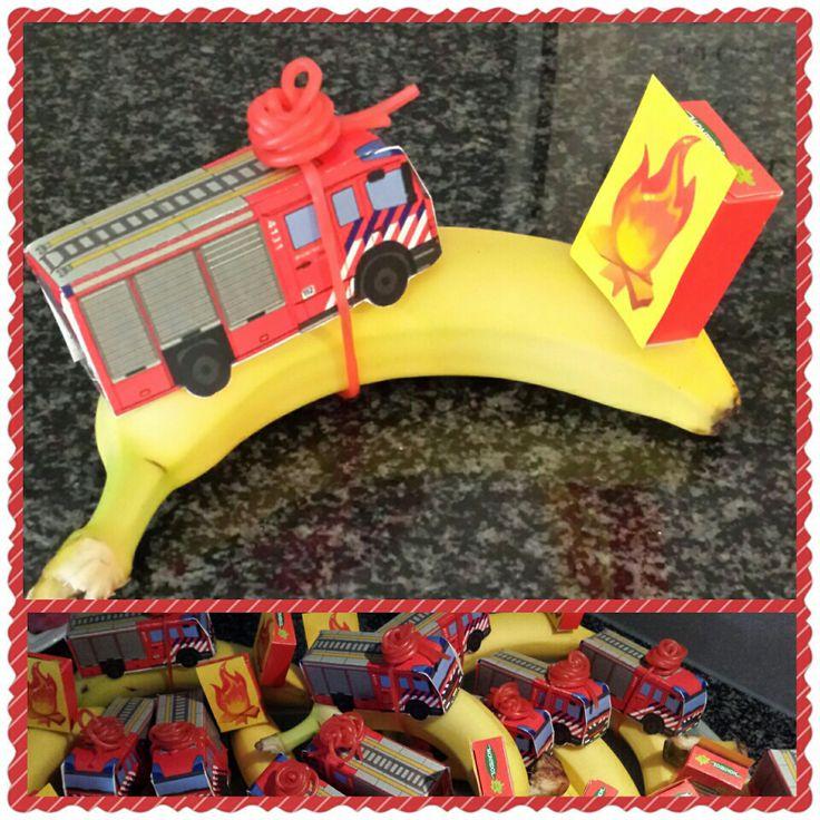 De brandweerwagen op wat dikker papier uitprinten, knippen, vouwen en lijmen. En met een rode dropveter vast maken aan de banaan als brandslang.  Op bv. Een doosje rozijnen een vlam plakken, en met een saté prikker prik je deze in de banaan.
