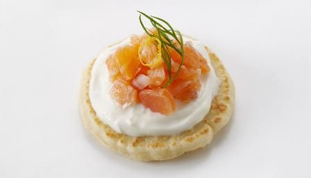 Smoked salmon tartare canapes with shallots, dill and soured cream on blinis