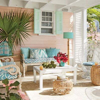 The back porch is framed in a cultivar of hibiscus brought to the island in the 1970s for a wedding. The sofas are whitewashed teak.