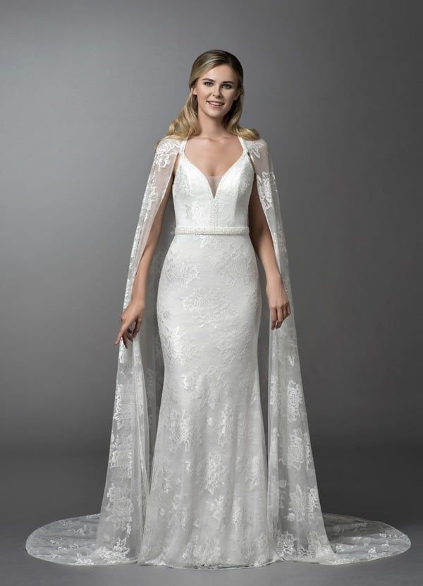 88f54fd7b8 Winter Wedding Dresses Fit For An Ice Queen. Smiling blonde woman wearing  white gown and cape in grey room