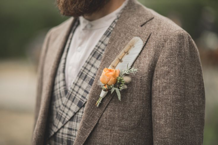 Boutonniere with a garden rose, bunny tail grass, silver foliage and an owl feather by Flying Bear Farm + Design www.flyingbearfarm.com - Photography by Martin + Stelling Photography