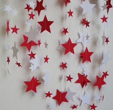Un rideau d'étoiles en papier Canson rouges et blanches montées sur fil de nylon à accrocher sur le mur pour une décoration de Noël fait maison