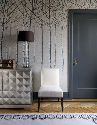 Silver & gray foyer design with gorgeous blue door, blue gray trees walls, silver chest, white chair, blue & gray rug and herringbone patterned wood floors.