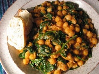 Chickpea and Spinach Tapas 10 ounces fresh spinach leaves, rinsed, or 1 (10-ounce) package frozen leaf spinach 19-ounce can (2 cups) chick-peas, drained and rinsed 1 red bell pepper, finely diced 1 tablespoon snipped fresh chives 1 to 2 lemons, juiced or to taste 1/4 to 1/3 cup extra virgin olive oil Salt and freshly ground black pepper, to taste