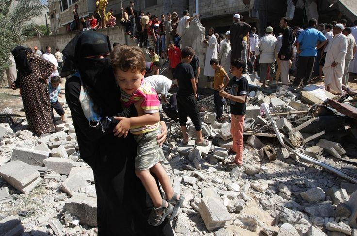 パレスチナ自治区ガザ地区(Gaza Strip)南部のハンユニス(Khan Yunis)で、イスラエル軍の空爆を受けたイスラム原理主義組織ハマス(Hamas)構成員の家屋のがれきを人々が調べる中、子どもを抱いて歩く女性(2014年7月8日撮影)。(c)AFP/SAID KHATIB ▼9Jul2014AFP|イスラエルのガザ軍事作戦で死者27人、負傷者100人超 http://www.afpbb.com/articles/-/3020039 #Khan_Yunis