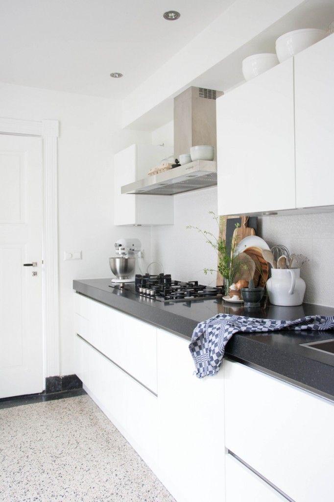 Weiße küche mit dunkler arbeitsplatte und terrazzoboden