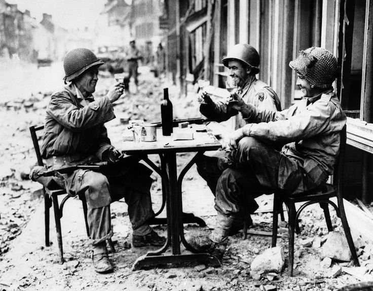 An American version of a sidewalk cafe, in fallen La Haye du Puits, France on July 15, 1944, as Robert McCurty, left, from Newark, New Jersey, Sgt. Harold Smith, of Brush Creek, Tennessee, and Sgt. Richard Bennett, from Wilkes Barre, Pennsylvania, raise their glasses in a toast. (AP Photo).