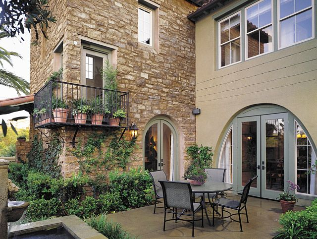 Rustic Stone Patio With Wrought Iron Accents And Seating