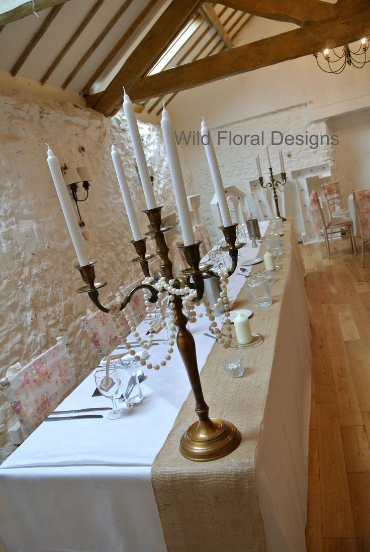 Bronze candelabra with hanging pearls, hessian table runners. Bickley Mill Inn wedding Devon.