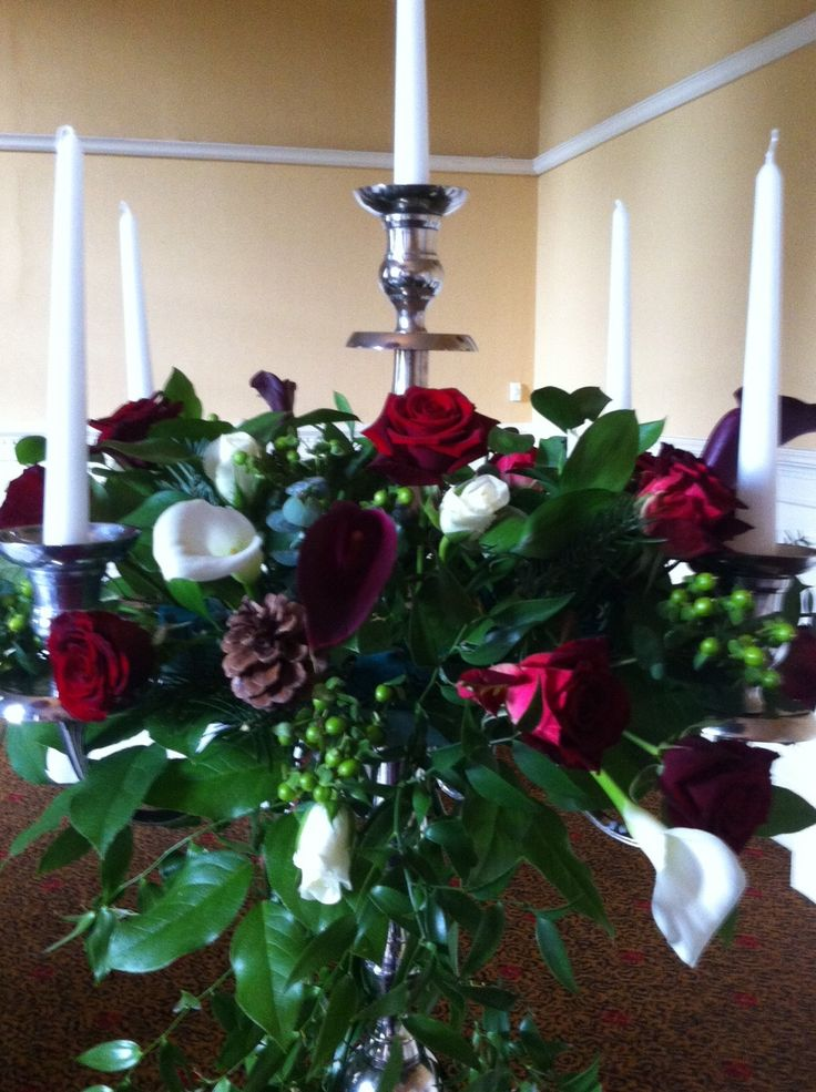 Silver candelabra with dark red and ivory flowers