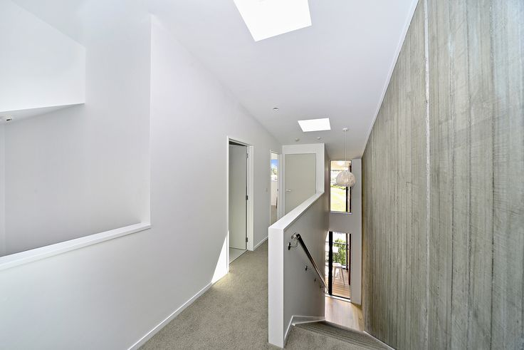 Bright white paint to create a spacious hallway, offset by the feature wooden wallpaper