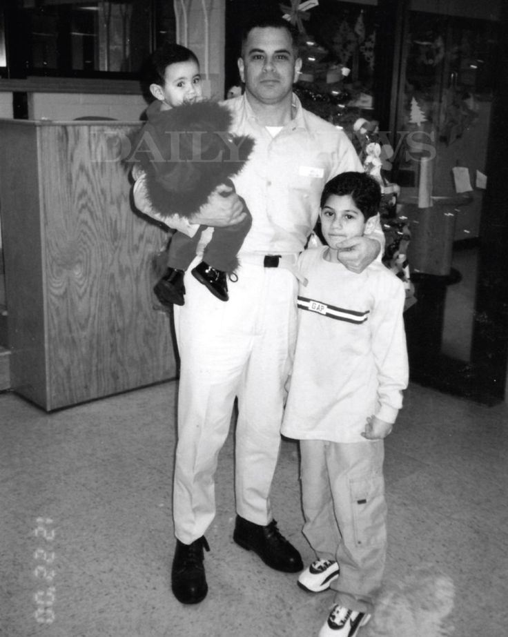 """Another image featured in the book """"Shadow of My Father"""" by John (Junior) Gotti shows John (Junior) Gotti with his son and holding his daughter while being held at Ray Brook Prision in 2000."""