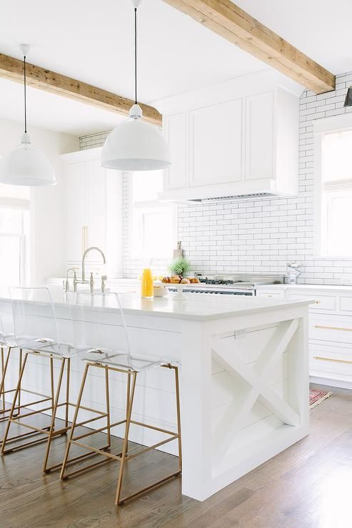 Brass and lucite counter stools are stat in front of a white shiplap island accented with an x-island side trim and topped with white quartz countertops holding a sink with a polished nickel deck mount gooseneck faucet illuminated by two modern white pendants hung from a exposed beam ceiling.