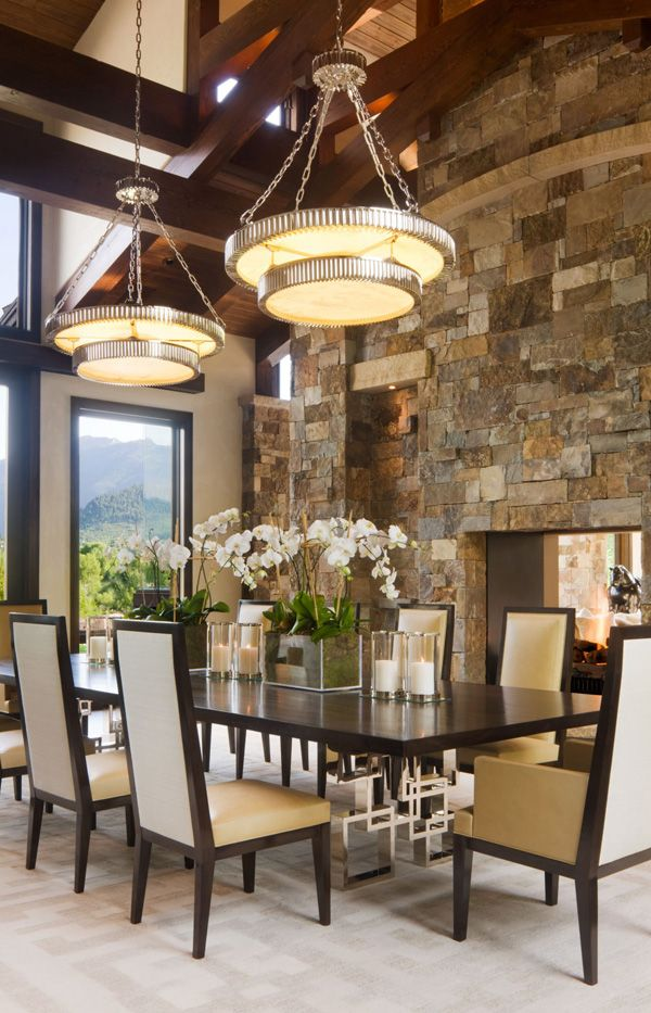 Luxurious Colorado mountain home. Like the mix of rustic stone wall w/ modern straight line furniture & round pendant lighting to introduce a circular shape into the space