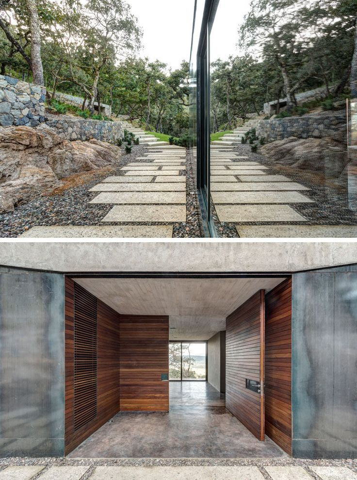 This modern house has a stone path that leads from the garage to the front entryway. The entryway, including the front door, are covered in wood, breaking up the harshness of the surrounding steel and the concrete overhead.