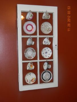 I love the old look decor in my home. I love antiques. I took an old cabinet door and cups and saucers and created this window decoration for my dining room wall. Hope you enjoy it!