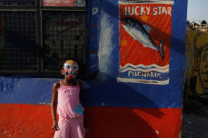 A girl wearing a mask stands outside a shop in Alexandra Township Credit: Kim Ludbrook/EPA