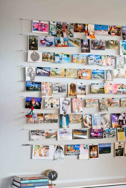 love this photo wall! one continuous piece of wire is strung along hooks, and photos/postcards are interchangeable using clips