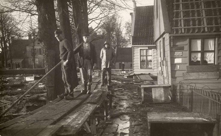 De watersnood van 1916. Ten noorden van Amsterdam, in Buiksloot, is een noodbrugje aangelegd. Overal ligt modder en hout. Buiksloot, Nederland, 1916.