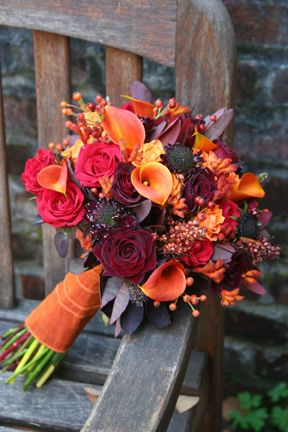 Fall themed wedding bridal bouquet featuring roses and lilies in a palette of red, orange and yellow.