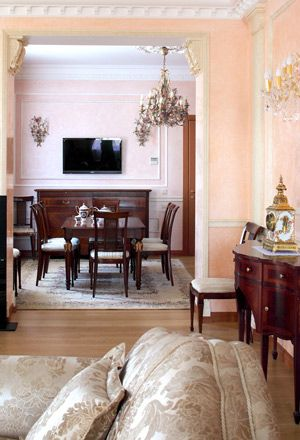 Для увеличения гостиной архитектор, с одной стороны, перенёс наружную стену, с другой—спроектировал эффектный открытый вид на столовую, отделанную лепниной. Комод, обеденный стол, стулья, Medea. Светильники, Mechini.