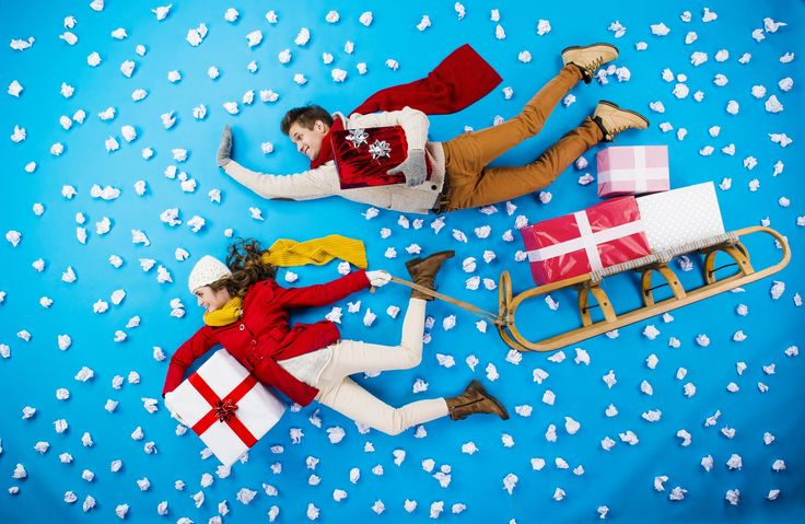Young couple on sledge with Christmas presents - Happy young couple on sledge with Christmas presents against the blue background with snowflakes