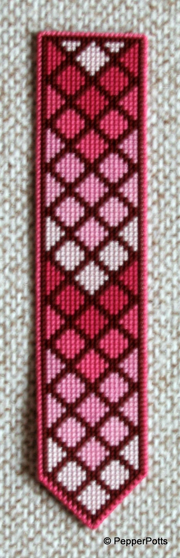 Worked on 14ct plastic canvas in a cross stitch, using various shades of raspberry red and pink stranded cotton leftovers. The diamonds were worked first, then the contrasting lines filled in in a very deep claret stranded cotton. It is backed with thin craft foam using a double sided adhesive film.