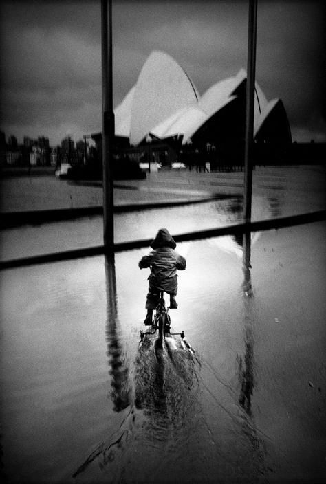 Trent Parke:: AUSTRALIA. Sydney. A young boy rides his tricycle through a puddle at Bennelong Point, with the Sydney opera house in the background. From Dream/Life series. 1998.