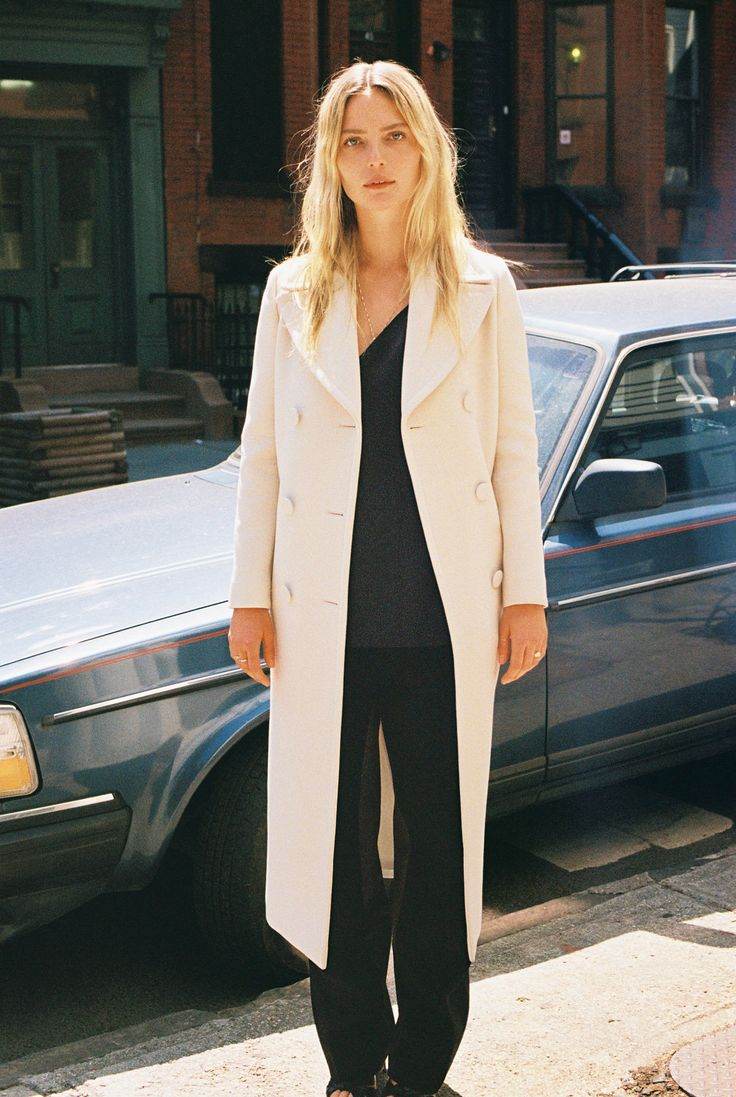 Camilla Deterre in a Gucci white belted coat, black slip top, and black trousers