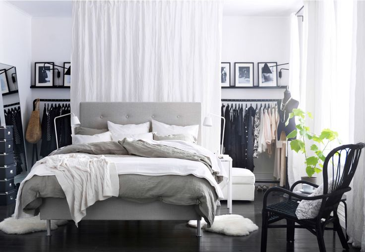 A modern bedroom with a large grey and  white bed in the center of a white and black room. Behind the bed a curtain makes a separate space for clothes