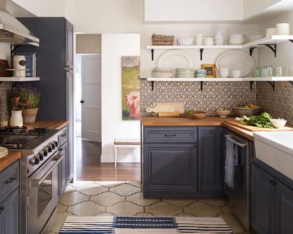 The graphic colorway puts a fresh, modern twist on the old-fashioned arabesque motif. Large-scale concrete floor tiles echo the curvy shape of the backsplash tile for a cohesive feel.