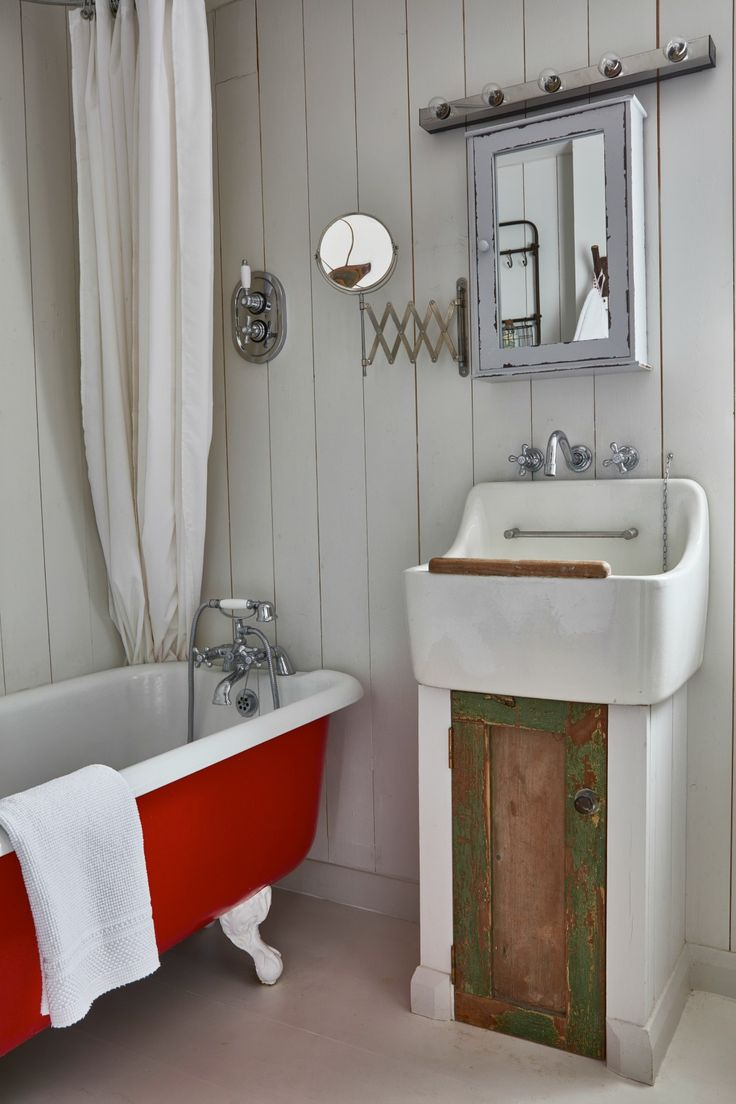 An old claw foot tubs gets a coat of red paint in this cottage bathroom with planked white walls kellyelko.com