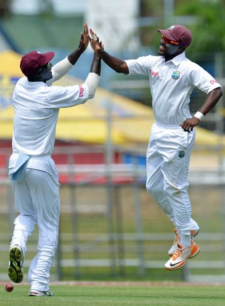 West Indies cricketers Darren Bravo (R) and Darren Sammy celebrate Bravo's catch of Australian batsman David Warner during the fourth day of the second-of-three Test matches between Australia and West Indies April 18, 2012 at Queen's Park Oval in Port of Spain, Trinidad.