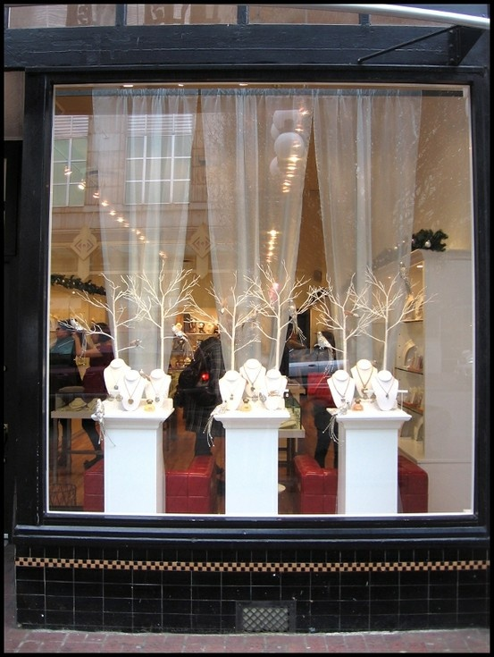 front window display using all white...like the tulle draped from the ceiling