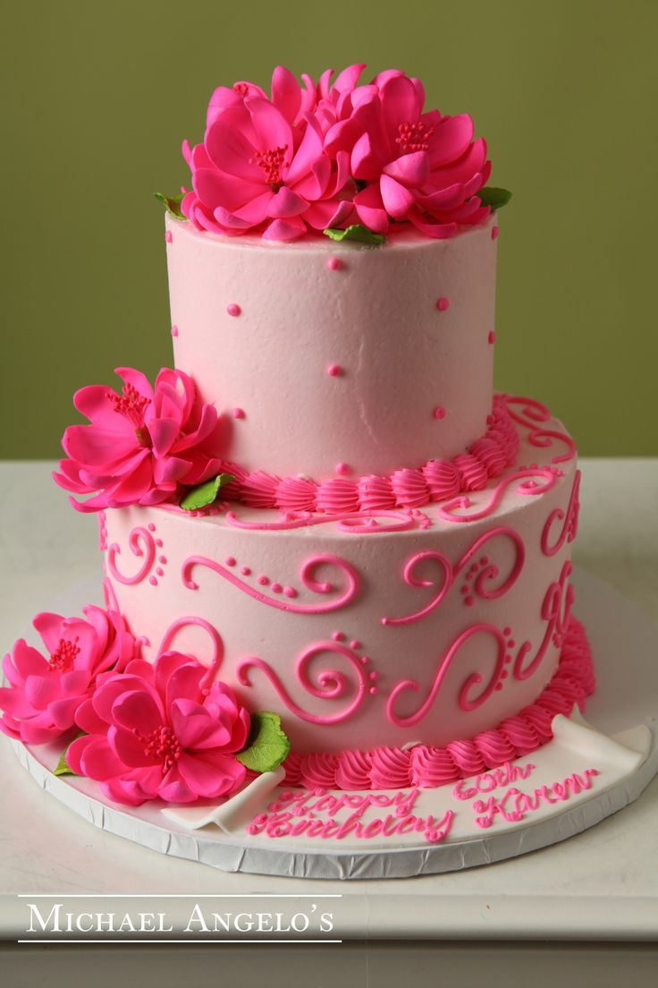 Pink Lotus #93Milestones This two-tier creation is iced in pink buttercream and accented with our popular swirls and dots. Gum paste lotus flowers are placed on top and the sides to add some depth. It's a beauty!