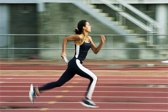 Mujer corriendo en una pista de atletismo