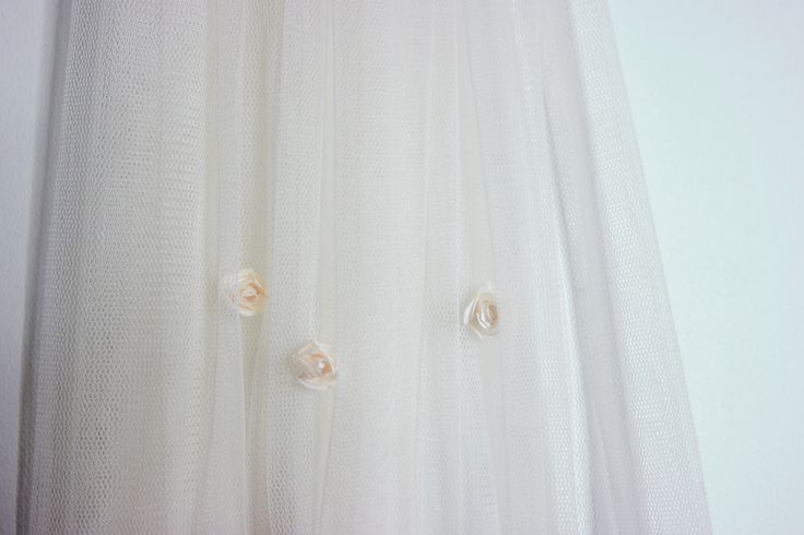With a gentle rain of small delicately made matching paper roses, Flora is our veil of flowers and spring. She is made of high quality English Net and the flowers are secure fastened - one and one by hand. Flora is a classic standard cut veil, and with a cathedral length she sweeps the floor gracefully. She is gently gathered at the top to a transparent comb with a row of paper flowers for that extra detail. Photo: Teres Arvidsson & Wenerskapet Model: Christine