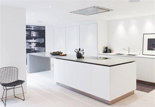 cocina moderna blanca, barra prolongación de isla con zona de cocción, sin muebles altos, módulo empotrado para electrodomésticos y almacenaje, suelo de parquet color natural