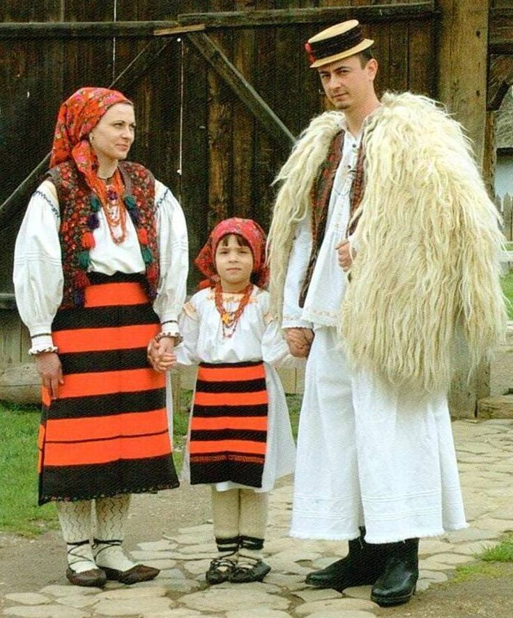 In the photo above (from Maramures), the mother is wearing two aprons and the daughter one. The aprons have wide, horizontal stripes in red and black and are tied at the waist with cords. The mother is wearing a sheepskin vest that opens at the front and is ornamented with tassels. Both the mother and daughter are wearing headscarves. Both are also wearing the traditional style of shoes and woolen socks.