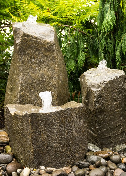 Water feature in the garden - a rock fountain is a great rustic water feature for a minimalist garden design