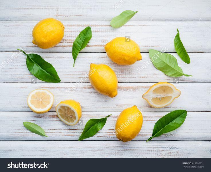 Fresh lemons and  lemons leaves on rustic wooden background. Fresh lemons and lemon slice on wooden table with flat lay.  Fresh citrus fruit background.