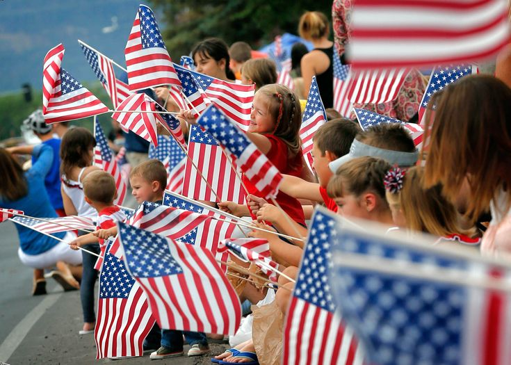Un grand nombre d'enfants agitant des drapeaux américains (© AP Images)