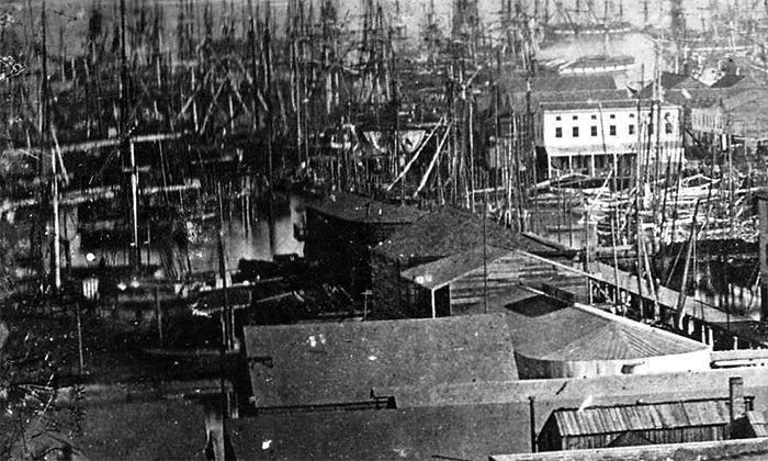 """After one of the frequent fires that ravaged San Francisco, in May 1850, the mercantile firm of E. Mickle & Co. purchased the General Harrison to serve as a """"storeship,"""" or floating warehouse. In 1851, however, San Francisco again caught fire: engulfing whole streets, the flames crumbled supposedly """"fire proof"""" brick buildings and swept under the wharves. More than 2,000 buildings were lost, including the storeships Niantic, Apollo, and General Harrison."""