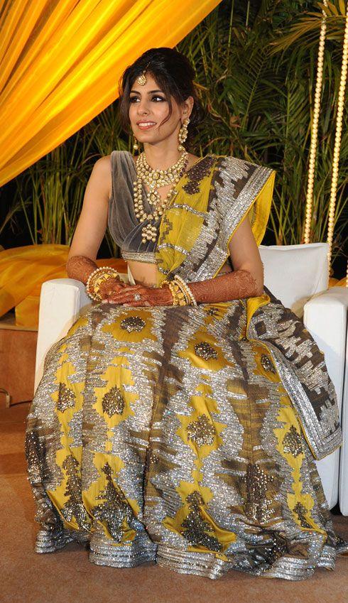 A grey and yellow combination raw silk lehenga studded with Swarovski crystals by Shantanu & NIkhil for the reception of Ashni Shah of WeddingSutra.